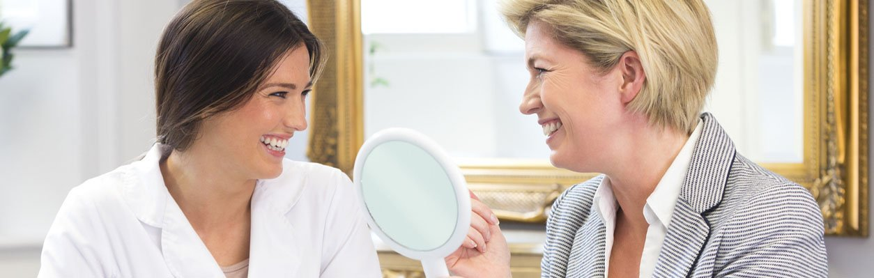 Doctor and patient smiling and looking in mirror