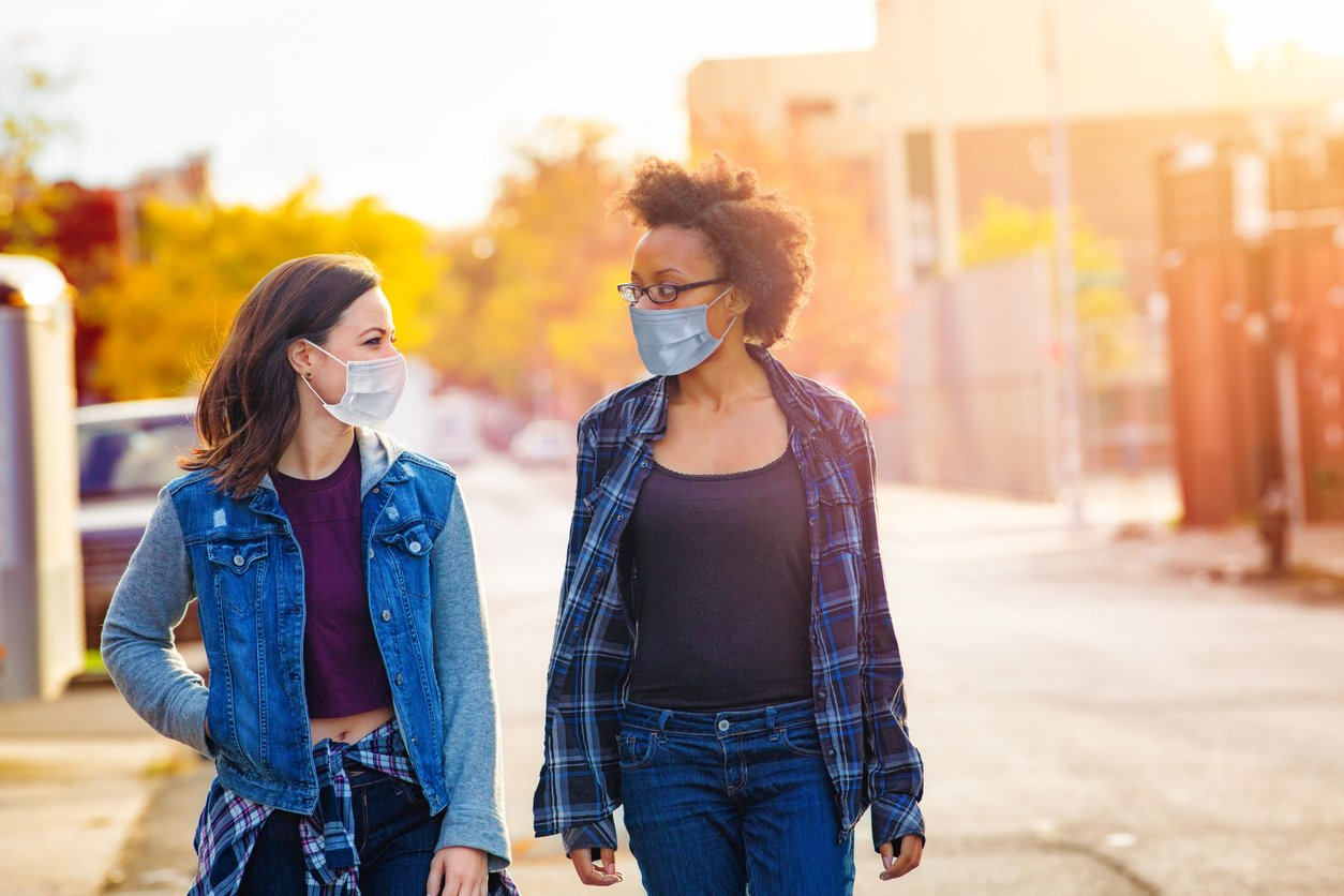 two women walking in a city with masks on