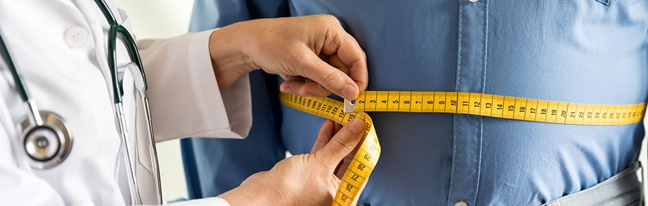 doctor with measuring tape around man's stomach