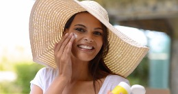 woman applying sunscreen with hat on