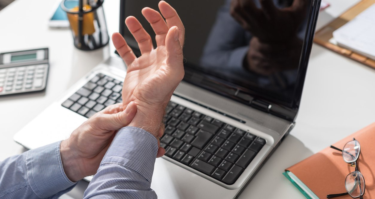 man grasping wrist over his laptop