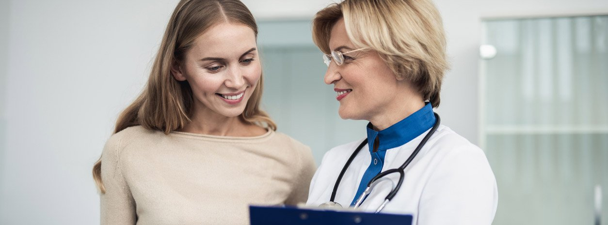 Woman doctor smiling at female patient