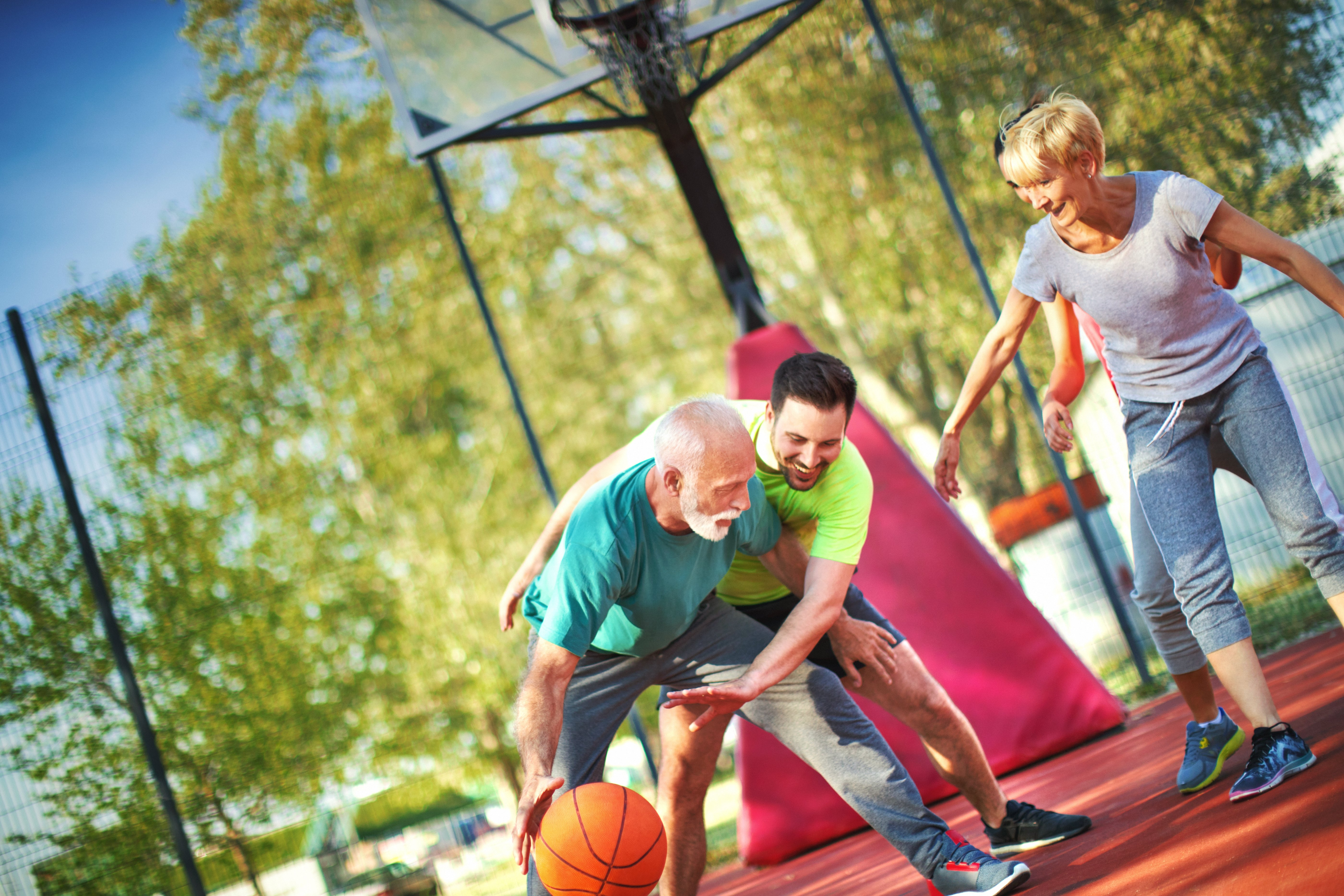 middle age parents playing basketball with adult child